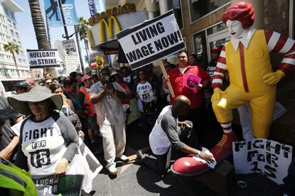 Robert Wideman, a maintenance mechanic at McDonalds Corp., shines the shoes of a Ronald McDonald statue outside of a restaurant while protesting with fast-food workers and supporters organized by the Service Employees International Union (SEIU) in Los Angeles, California, U.S., on Thursday, Aug. 29, 2013. Fast-food workers in 50 U.S. cities plan to walk off the job today, ratcheting up pressure on the industry to raise wages and demanding the right to wages of $15 an hour, more than double the federal minimum of $7.25.