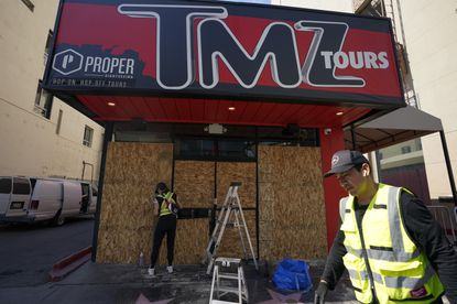Ashley Barker and Nick Valdez cover windows with boards at TMZ Tours on Wednesday, June 3, 2020, in the Hollywood area of Los Angeles in response to protests over the death of George Floyd. Floyd died in police custody on Memorial Day in Minneapolis. (AP Photo/Ashley Landis)
