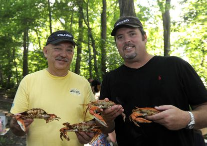 "Jay Shiba, left, and Nick Thomas, right, hold some of their crabs at the annual crab cooking challenge called ""War By The Shore"" at the home of Jay Shiba. Guests choose which is better: Maryland steamed crabs or Gulf Coast-style boiled crabs. Jay's crabs were steamed; Nick's were boiled."