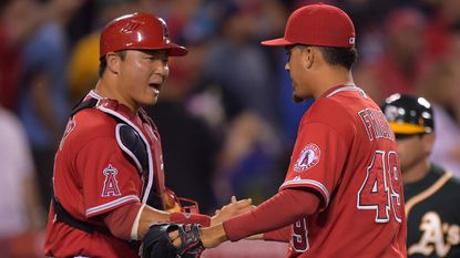 Angels catcher Hank Conger, left, congratulates closer Ernesto Frieri following the team's 4-1 win over the Oakland Athletics on Monday. The Angels managed to move closer to the Athletics at the top of the AL West following this week's series with Oakland.