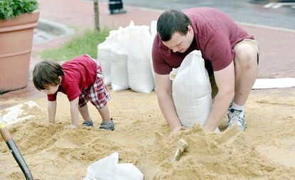 Avery Adams, 2, plays in the sand as his father, Zachary Adams, fills sandbags on Broadway Square.