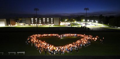 """A crowd of people honoring Robert """"Bird"""" Brown gather on the field at Westminster High School Tuesday evening, April 27, 2020, during a memorial gathering to remember the popular Westminster High School counselor, coach and teacher who passed away unexpectedly Monday."""