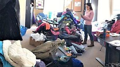 Melissa DiDonato, principal of Padonia International Elementary, sorts through coats, hats, and gloves that she will be able to offer to students in need.