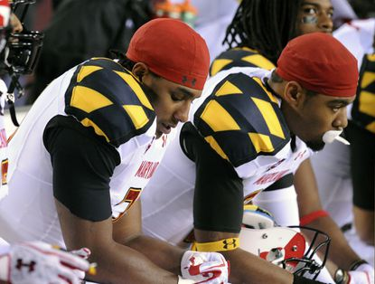 Maryland's Jeremiah Wilson (left) and Devin Burns react on the bench to Notre Dame's final touchdown, which made the score 45-21.