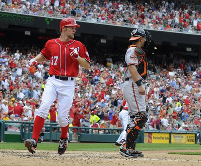 Nationals starter Stephen Strasburg crosses home plate in front of Orioles catcher Luis Exposito in the third inning.