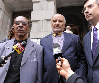 Walter Lomax, shown here at left in 2014 with his lawyers after being exonerated for a crime he did not commit, suffered a heart attack in the Miller Senate Office Building Wednesday. He was revived by Frederick County Sheriff Chuck Jenkins and Trooper First Class Luke Rafer of the Maryland State Police.