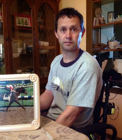 Former jockey Jose Villegas poses at his Hampstead home next to a photo from when he was an exercise rider. Villegas became paralyzed below the waist as the result of a spill at Laurel in September 2013.