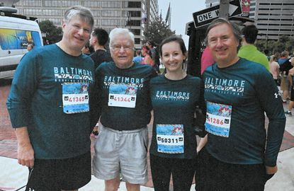 Bob Gralley, 93, of Parkville, with his sons, Kevin, left, and Craig, right, and granddaughter, Sara Petry, at a recent marathon. Gralley will run his 19th half-marathon in the upcoming Baltimore Running Festival. His sons, Craig and Kevin, and granddaughter, Sara Petry, will join him. Gralley has also completed 42 marathons. Oct. 15, 2019