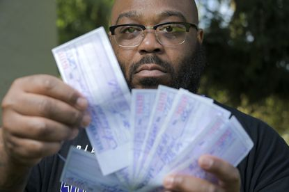 Irvin Haygood looks through receipts that he paid at his Dundalk apartment as he fights to regain his life with the weight of daily house arrest charges that destroyed his finances Fri., Aug. 28, 2020. (Karl Merton Ferron/Baltimore Sun Staff)