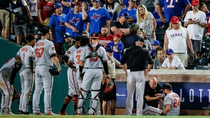 Baltimore Orioles right fielder DJ Stewart (24) is helped up by a trainer after awkwardly falling down attempting to catch a foul ball hit by Texas Rangers shortstop Elvis Andrus, not pictured, during the sixth inning Wednesday, June 5, 2019, in Arlington, Texas.