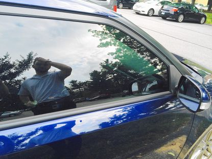 John Truit is reflected in the passenger side window as he surveys damage to his 2011 Scion TC from a June 23 hail storm.