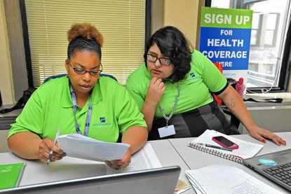 Pamela Williams, left, and Angela Flores are among the 14 new navigators who will help people sign up for insurance coverage with the Maryland Health Exchange.