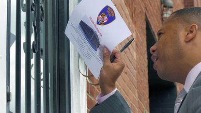 Detective Sgt. Lamar Howard asks a resident to open his door to take a flier as he and Detective Alexi A. Correa distribute them door-to-door in West Baltimore.