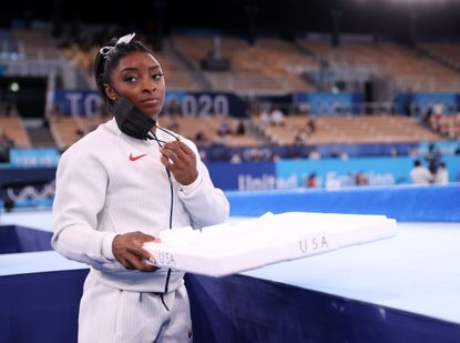 TOKYO, JAPAN - JULY 27: Simone Biles of Team United States supports her team mates by carrying their chalk after pulling out after the vault during the Women's Team Final on day four on day four of the Tokyo 2020 Olympic Games at Ariake Gymnastics Centre on July 27, 2021 in Tokyo, Japan. (Photo by Laurence Griffiths/Getty Images)