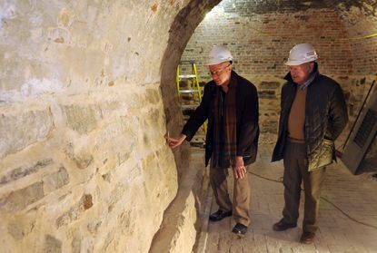 Dr. Lance Humphries, left, chairman of the Mt. Vernon Place Conservancy, looks at a wall inside the Washington Monument with Fred Eisenbrandt, right, a historic building restoration contractor.