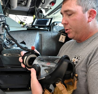 Abingdon Firefighter Ryan Githens shows how the adapter he designed for N95 COVID filters fits onto the typical facemask for firefighters.
