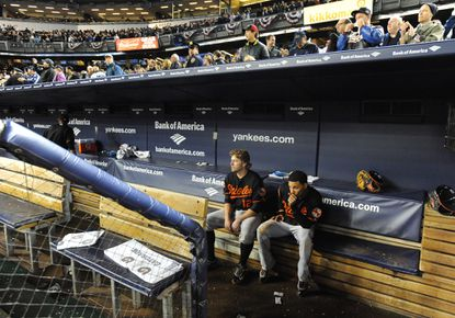 Dejected Orioles Mark Reynolds (#12), left, and Robert Andino, right, sit in an empty Orioles dugout while watching the Yankees celebrate on the field. The Yankees defeated the Orioles by score of 3 to 1 in game five of the ALDS at Yankees Stadium.