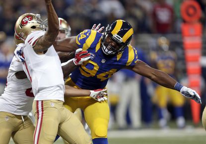 San Francisco 49ers quarterback Colin Kaepernick, left, throws under pressure from St. Louis Rams defensive end Robert Quinn during the first quarter,Sunday, Nov. 1, 2015, in St. Louis.