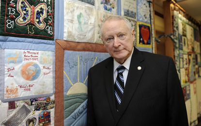 Frank Weathersbee is retiring as Anne Arundel County State's Attorney. He will be joining the Maryland Parole Commission. Here, he stands with a quilt that is on display in his office. It was made by the families of crime victims to honor their memories.