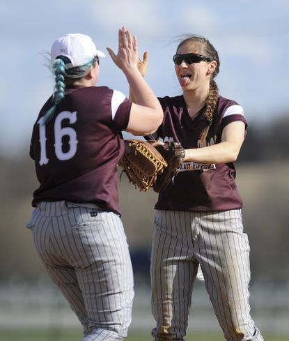 Winters Mill pitcher Zoey Deniker high fives Megan Harman during their game against South Carroll in Winfield Tuesday, April 4, 2017.