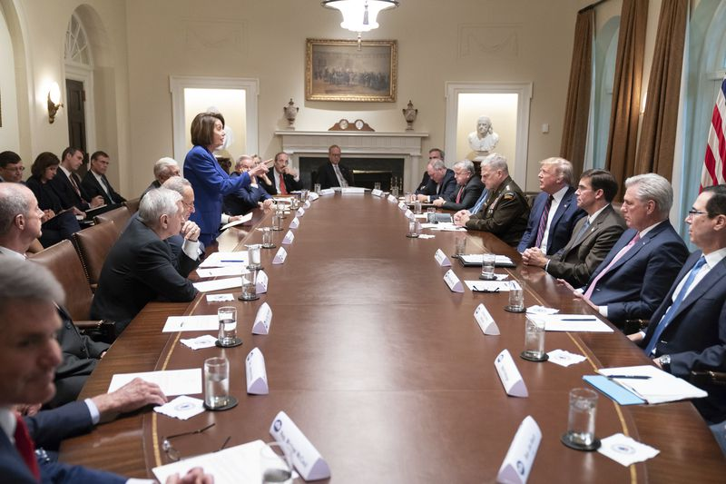 In this photo released by the White House, President Donald Trump, center right, meets with House Speaker Nancy Pelosi, standing left, Congressional leadership and others, Wednesday, Oct. 16, 2019, in the Cabinet Room of the White House in Washington.
