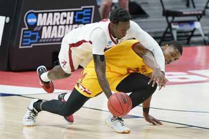 Alabama's Juwan Gary, top, dives over Maryland's Jairus Hamilton, bottom, to reach a loose ball during the first half of a college basketball game in the second round of the NCAA tournament at Bankers Life Fieldhouse in Indianapolis Monday, March 22, 2021. (AP Photo/Mark Humphrey)
