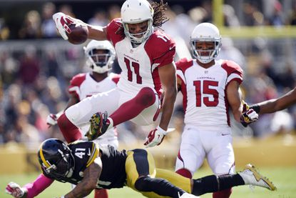 Arizona Cardinals wide receiver Larry Fitzgerald (11) leaps over Pittsburgh Steelers cornerback Antwon Blake (41) after making a catch, Sunday, Oct. 18, 2015 in Pittsburgh.