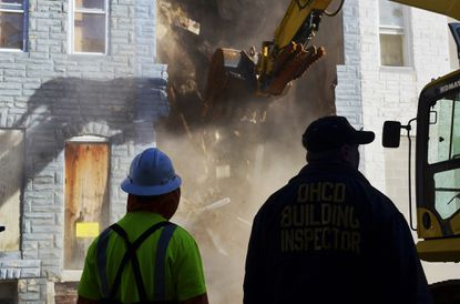 A vacant rowhouse is torn down at a press event announcing Project C.O.R.E.