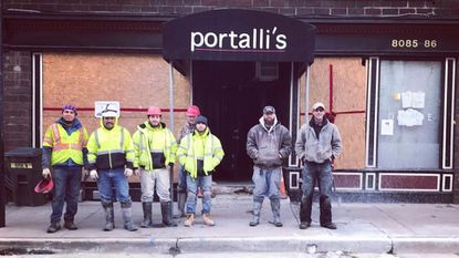 Workers stand outside Portalli's in Ellicott City in late 2016. The restaurant was severely damaged by flooding in July 2016 and will reopen Dec. 1.
