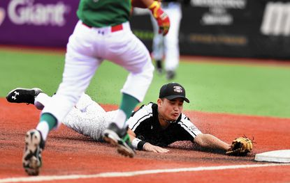 New Zealand's Huriwaka Repia dives to firstbase to make the play for an out on the Mexico baserunner during Monday's game between Mexico and New Zealand on Cal Sr.'s Yard.