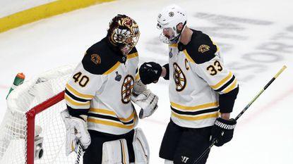 Boston Bruins goaltender Tuukka Rask congratulates defenseman Zdeno Chara on his empty-net goal during Game 6 of the Stanley Cup Final on June 9.