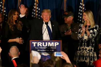 Republican presidential candidate Donald Trump speaks as his wife Melania Trump and daughter Ivanka Trump look on after primary day at his election night watch party in Manchester, New Hampshire. Trump was projected the Republican winner shortly after polls closed.