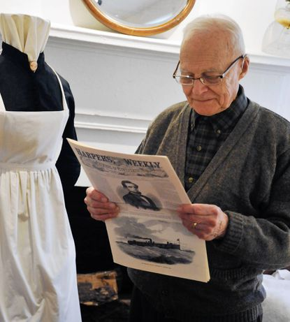 Former Laurel resident and Laurel Museum founding member Richard Compton, of Washington, reads a replica of the Sept. 6, 1862 Harper's Weekly newspaper at the Laurel Museum's exhibit.