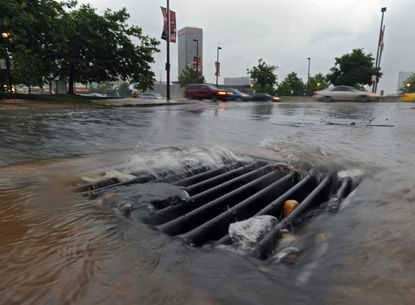 Baltimore, Md. -- Rain water rushes into a storm drain at Light street as a severe thunder storm passed through downtown Baltimore last year causing a heavy downpour during the evening rush hours.