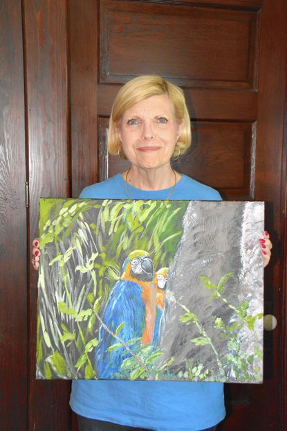 Alice Faber shows her painting of parrots that will be on exhibit at the Carroll County Arts Council Members Show through Nov. 8.