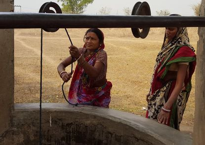 Two women draw water from a dug well, a typical rural source of unfiltered water, in Purulia District in eastern India. Local Rotary Clubs have helped with a project to give 17 schools and a village there clean water.
