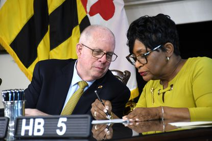 Maryland Gov. Larry Hogan, at left, speaks with House of Delegates Speaker Adrienne A. Jones during a bill signing ceremony at the State House in Annapolis on Tuesday, May 18, 2021. Delegate Jones is the first woman ever chosen to lead a chamber of the Maryland General Assembly.