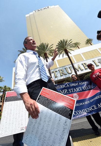 Democratic presidential candidate Martin O'Malley holds a copy of a petition signed by Trump International Hotel & Tower Las Vegas workers asking to be allowed to decide on union representation, as he speaks while standing in a median in front of the resort on Aug. 19 in Las Vegas.