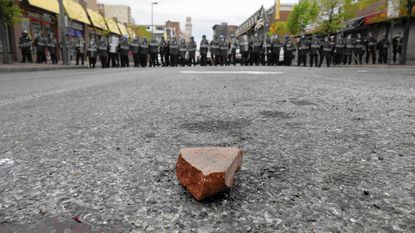 A brick rests in the middle of Eutaw Street as police guard Lexington Market during an uprising following the death of resident Freddie Gray, 25, after he was taken into police custody.