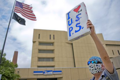 A demonstrator holds a sign in support of the U.S. Postal Service during an Aug. 22, 2020, protest outside Baltimore's main post office facility on Fayette Street. It's the site of the Baltimore Processing & Distribution center, where an audit found 68,000 pieces of political mail sat untouched for five days during the runup to the June 2 primary.