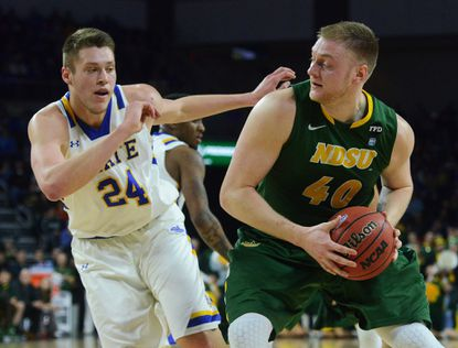 North Dakota State's Dexter Werner (40) looks around South Dakota State's Mike Daum (24) on his way to the net during an NCAA college basketball game for the Summit League men's tournament championship, Tuesday, March 8, 2016, in Sioux Falls, S.D. (Elisha Page/The Argus Leader via AP)