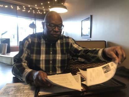 Otis Collins, president of the Halethorpe Civic League, reviews material compiled on the former Halethorpe Colored School on Northeast Avenue Feb. 5 at Oca Mocha. The league nominated the old schoolhouse, which is now managed by Baltimore County Department of Recreation and Parks, to be added to the county's historic landmark list.