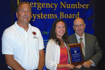 Allison Mosley, center, accepts her award of top telecommunicator for 2014 from John Woelfel, president of the Maryland Emergency Number Association, left, and William Frazier, representing the Emergency Number System Board.