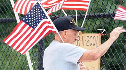Leroy Edmunds Jr. of Joppa proudly waves as he stands next to his hand made tribute to those who were killed on September 11 2001 as he and other gather at the Old Mountain Road ovepass at I-95 in Joppa Monday to wave flags in remembrance of the event.