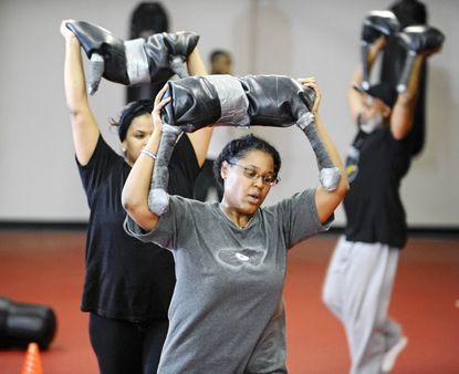 Monica Stevens, of Pikesville, and others lift about 18 pounds while running during Soldierfit workout. Soldierfit is a new boot-camp style exercise class modeled after military training.