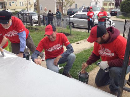 Volunteers paint steps at rowhomes on Soellers Point Road in Turner Station as part of Rebuilding Together Baltimore events Saturday. (Jessica Anderson/Baltimore Sun)