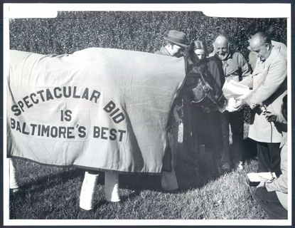 In 1979, Spectacular Bid is offered a token of the city's appreciation by Mayor William Donald Schaefer, far right, at Pimlico. Spectacular Bid won two legs of racing's triple crown. Looking on are trainer Buddy Delp and owners Teresa and Harry Meyerhoff (between his wife and Sschaefer). File