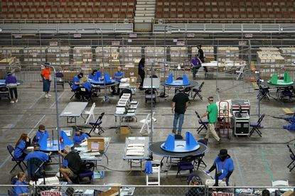 In this May 6, 2021 file photo Maricopa County ballots cast in the 2020 general election are examined and recounted by contractors working for Florida-based company, Cyber Ninjas, at Veterans Memorial Coliseum in Phoenix. (AP Photo/Matt York, Pool,File)