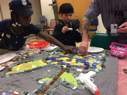 """Ariyonna Pritchett, 7, and Sebastian Taylor, 6, help build a peace-themed mosaic that will feature toy guns surrendered by East Baltimore children in exchange for nonviolent toys. The exchange and art project are the centerpiece of a Halloween party at the St. Frances Academy Community Center that also celebrates the 10-year-anniversary of a Baltimore """"peace camp"""" that teaches children conflict resolution."""