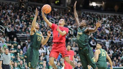 Anthony Cowan Jr. drives to the basket defended by Miles Bridges and Lourawls Nairn Jr. of Michigan State at Breslin Center on Thursday in East Lansing, Mich.